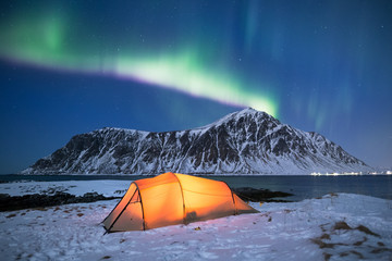 Illuminated tent under a beautiful northern light display on Lofoten islands in Norway