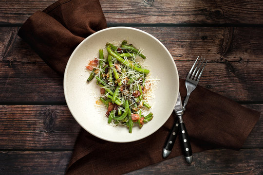 Green beans with bacon and cheese on dark wooden table