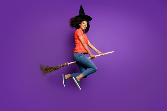 Full length body size side profile photo of cheerful funny witch riding a broomstick expressing emotions wearing orange t-shirt jeans denim cap headwear flying jumping isolated vivid color violet