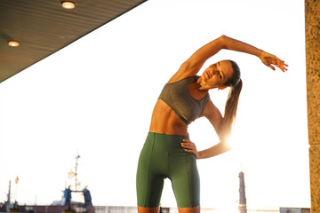 Image of seductive athletic woman doing exercises while working out