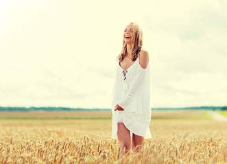 country, nature, summer holidays, vacation and people concept - smiling young woman in white dress...