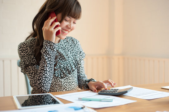 Accountant or female secretary is using the phone while working. Female businessmen are talking on the phone while using a calculator.