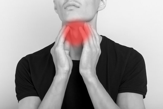 Sick asian man suffering from sore throat. Causes include flu, common cold, bacterial infections, allergies, smoke, GERD or tumor