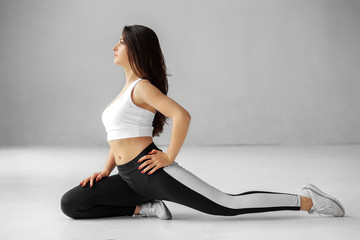 Young adult girl is engaged in stretching. Sportswear. The concept of sports, healthy lifestyle, fitness, stretching.
