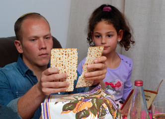 Jewish Family Celebrating Passover.Jewish man blessing on Matzah as they celebrate Seder. The feast is celebrated on the first night of Passover, holiday commemorating the Jews exodus from Egypt.