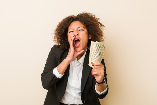 Young african american woman holding dollars shouting excited to front.