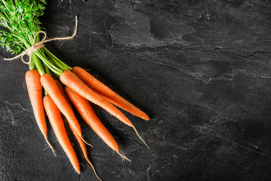 Fresh carrot on dark stone table or black background top view.