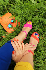 Colorful bright manicure and pedicure in different pink and orange sandals, and different blue and yellow pants on a background of green grass with glasses and a bag.Fashion accessories and summer nai