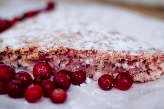 Cake or baked pudding of cottage cheese with red bilberry on white baking dish on wooden background