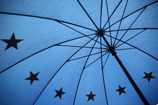 An umbrella with the pattern of the EU flag is seen outside the Houses of Parliament in London