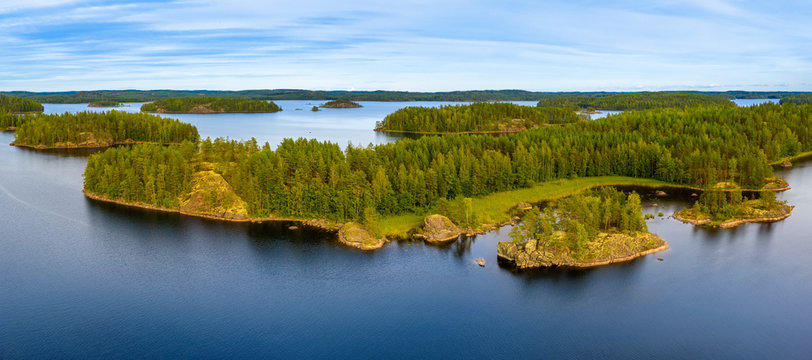 Aerial view of of small islands on a blue lake Saimaa. Landscape with drone. Blue lakes, islands and green forests from above on a cloudy summer morning. Lake landscape in Finland.