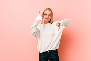 Young blonde teenager woman showing thumbs up and thumbs down, difficult choose concept