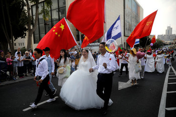 A bride and her groom celebrate, together with thousands of foreigners who support Israel, during an annual parade on the Jewish holiday of Sukkot in Jerusalem