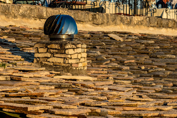 Rotating metallic with blue shades spinner chimney vent on stone tiled roof, Saranda, Albania, photo taken in the golden hour of spring evening