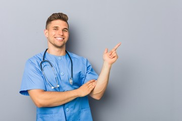 Young nurse man smiling cheerfully pointing with forefinger away.