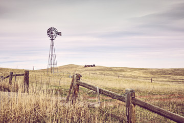 Foto auf Gartenposter Beige American countryside with an old windmill tower, color toning applied, USA.