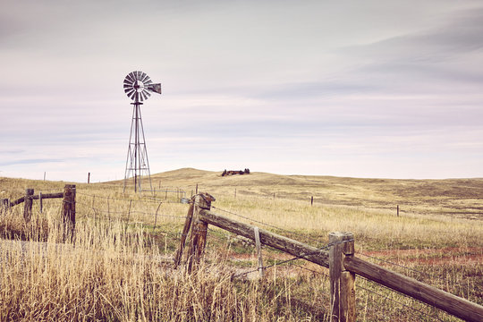 American countryside with an old windmill tower, color toning applied, USA.