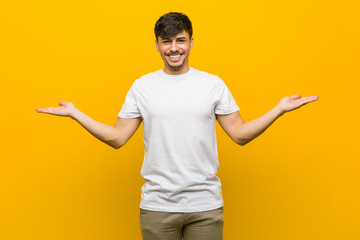 Young hispanic casual man makes scale with arms, feels happy and confident. Wall mural