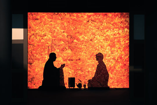 Silhouette of monk and Tea ceremony with blur red maple leave background.,  Zen and the Art of Tea concepts.