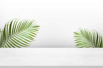 white wooden table top with green palm leave for product advertisement display on white background Wall mural