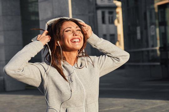 Young woman in gray hoodie enjoys music via earphones on the street
