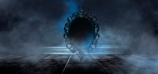 Dark night magic scene. Magic old mirror in a metal frame on a wooden tabletop. Smoke, magic, magical experience, a fabulous night. Blue neon, moonlight at night.