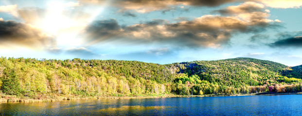 Panoramic aerial view of lake and trees in autumn foliage seaon against blue sky