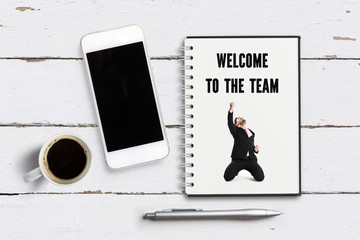 """notepad with message """"welcome to the team"""" with image of a happy businessman on wooden background"""