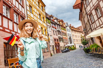 Young asian woman tourist traveling with german flag near the famous half-timbered street in Nuremberg old town Fotomurales