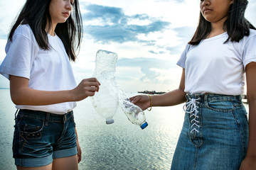 two asian teenager holding old waste plastic bottle standing on sea beach for ocean environmental issue