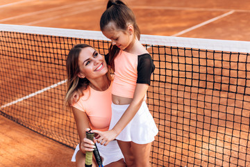 Loving mother holds her daughter and tennis rackets
