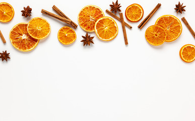 Christmas composition with dried oranges and spices on white background. Natural food ingredient for cooking or Christmas decor for home. Flat lay.