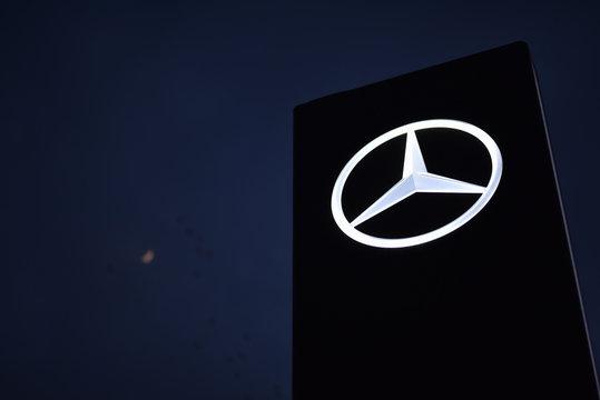 Kiev / Ukraine - 04.10.19: Logo of Mercedes-Benz car showroom in night on background moon and flight birds