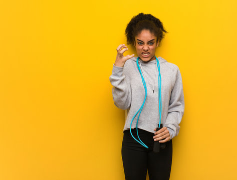 Young fitness black woman angry and upset. Holding a jump rope.