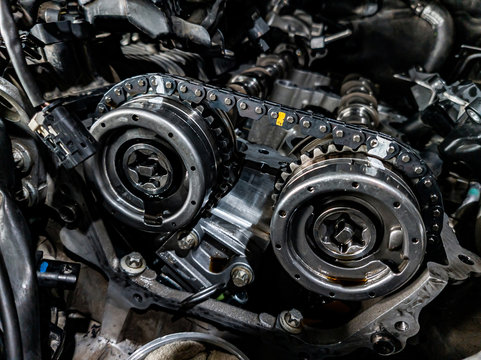 Close-up on a disassembled engine with a view of the gas distribution mechanism, chain, gears and tensioners during repair and restoration after a breakdown. Auto service industry.