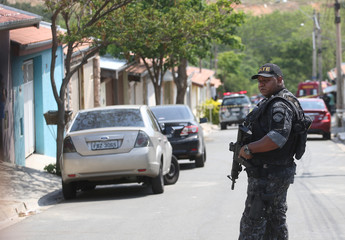 A police officer is seen near a site where an armed gang holds people hostage after they robbed a securities company at the Viracopos airpoart freight terminal, in Campinas