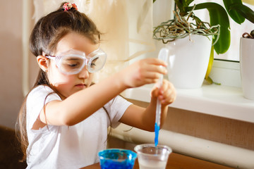 Little girl experimenting in elementary science class with protective gloves and glasses