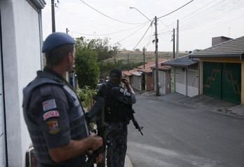 Police officers are seen near a site where an armed gang holds people hostage after they robbed a securities company at the Viracopos airpoart freight terminal, in Campinas