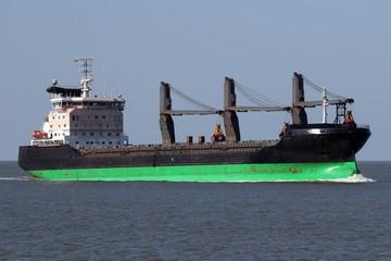 schwarzes Frachtschiff mit Ladekränen