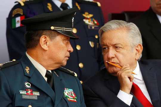 Mexico's President Andres Manuel Lopez Obrador and Secretary of Defence Luis Sandoval chat during an official event to mark the beginning of the construction of a new international airport, at the Santa Lucia military airbase in Zumpango