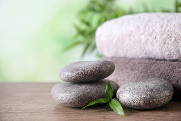 Poster de jardin Spa Composition with spa stones and towels on wooden table against blurred background. Space for text