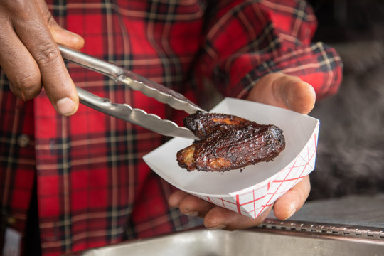 Placing Louisiana chicken wing in small paper tray with tongs