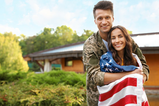 Man in military uniform with American flag and his wife outdoors