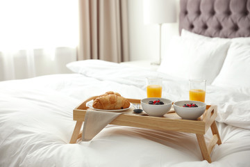 Tray with tasty breakfast on bed in light room
