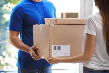 Woman receiving parcels from courier on doorstep, closeup