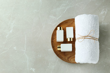 Top view of wooden tray with cosmetic bottles and towel on light grey marble table, space for text....