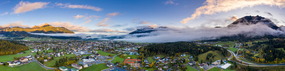 Foto op Canvas Panoramafoto s dawn panorama of reutte village at fall with clouds and mountains