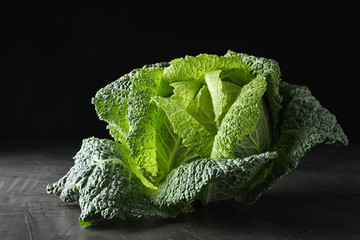 Fresh green savoy cabbage on grey table against black background