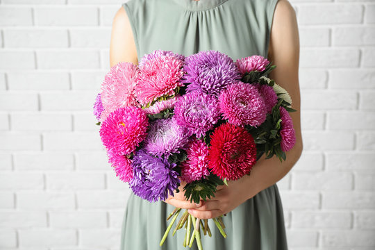 Woman holding bouquet of beautiful aster flowers against white brick wall, closeup