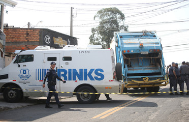 Police officers are seen near a site where an armed gang holds people hostage after they robbed a securities company at the Viracopos airport freight terminal, in Campinas